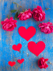 Big and small hearts and many red rose on the blue