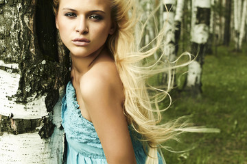 Beautiful blond woman in forest. flying hair