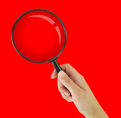 Hand holding magnifying glass on red background