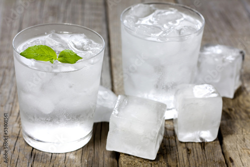 Glass of water with ice cubes on vintage wooden planks
