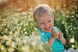 on the nature of the little baby playing and smiling on a field