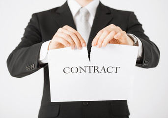 man hands tearing contract paper