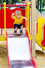 Positive little boy is about to go down from the slide