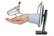 Computer monitor and hand with shopping cart