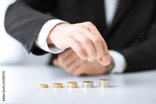 man putting stack of coins into one row