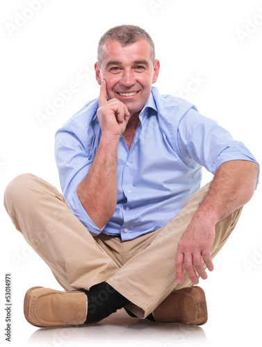 casual middle aged man sits pensive