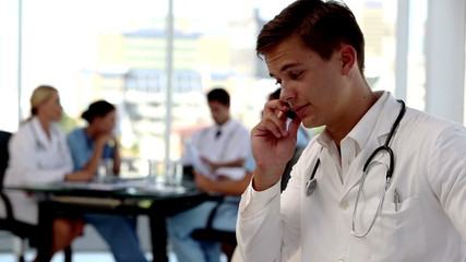 Focus on a doctor phoning besides colleagues