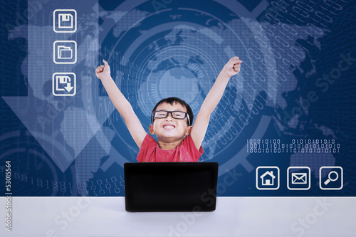 Asian boy winning using laptop on blue background