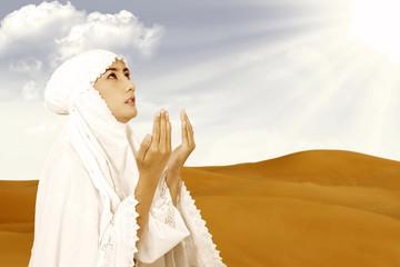 Asian female muslim in white praying at desert