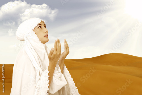 Asian female muslim in white praying at desert