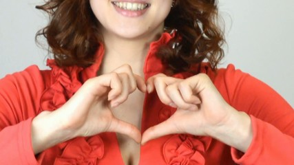girl shows heart; gesture