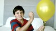 Boy piercing his yellow balloon and getting a fright