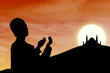 Card design silhouette of muslim man praying at sunset