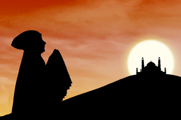 Silhouette of muslim woman praying near mosque