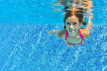 Happy active child swims underwater in pool
