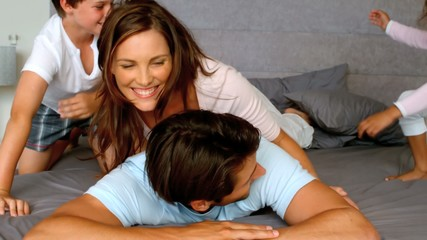 Family playing together in bedroom