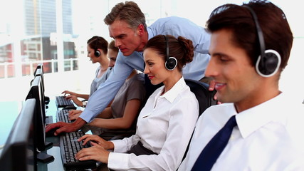 Smiling business people working in a call centre