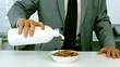 Businessman pouring milk into his cereals