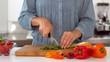 Woman slicing spring onion with knife