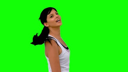 Athletic woman tossing her hair against green screen