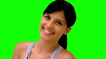 Athletic woman smiling at camera on green screen