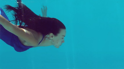Brunette woman swimming underwater in blue bathing suit
