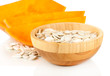 Pumpkin seeds in wooden bowl isolated on the white