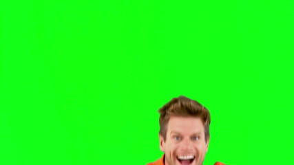 Attractive man jumping in front of the camera on green screen