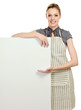 A smiling woman wearing apron and posing behind a white blank