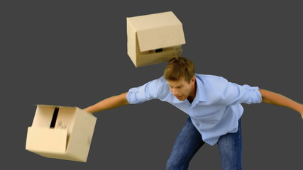 Clumsy man dropping boxes down on grey screen