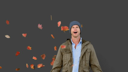 Amazed man looking at falling leaves on grey screen