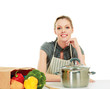 Woman in apron sitting on the desk with grocery bag