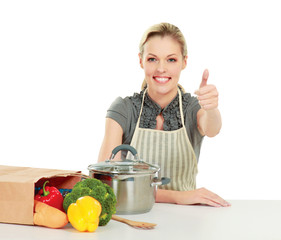 Woman in apron sitting  with grocery bag and showing ok