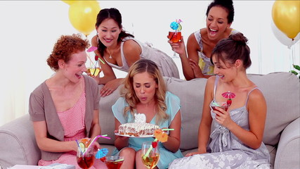 Woman blowing out the birthday candles surrounded by her friends