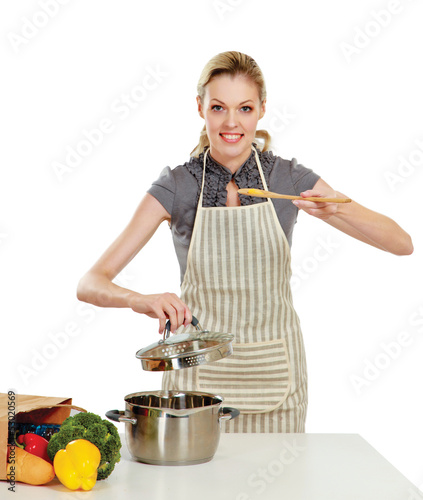 Woman standing on a kitchen and holding a spoon
