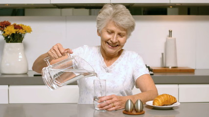 Happy woman pouring a glass of water for breakfast