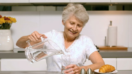 Retired woman pouring a glass of water for breakfast