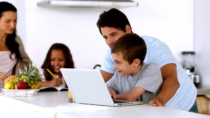 Father looking at laptop with son