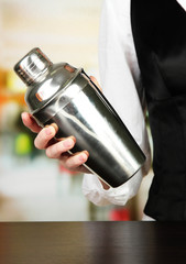 Barmen hand with shaker, on bright background