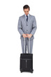 Serious young businessman waiting with his suitcase