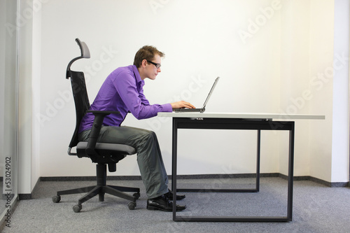 shortsighted businessman bad sitting posture at laptop