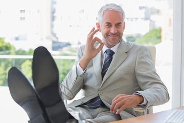 Smiling businessman giving ok sign