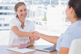 Smiling interviewer shaking hand of an applicant