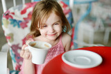 Adorable little girl drinking hot chocolate