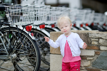 Adorable girl standing by a row of bicycles