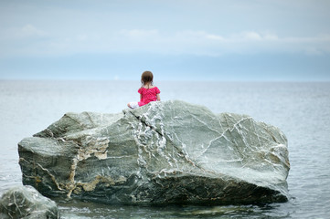 Adorable little girl sitting on a rock