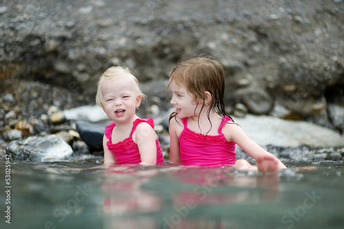 Two little sisters relaxing in hot spring