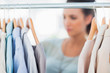 Fashion woman choosing clothes on clothes rail
