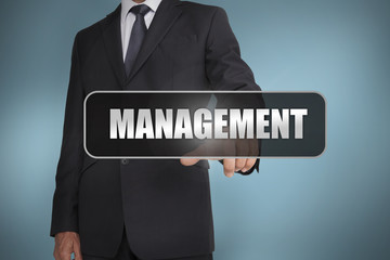 Businessman touching the word management written on black tag