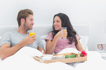 Beautiful couple having breakfast in bed